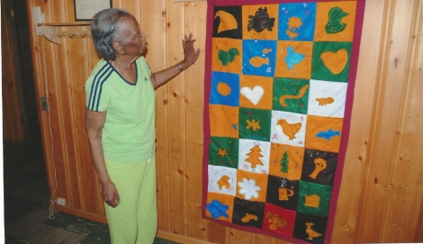 "Dr. Robbie Bean stands next to the family-themed quilt she received at the April Celebration of Families-Students Inc. event, from third graders from the Marie L. Greenwood Academy (incidentally, the school is named after the first African-American woman hired there, who is still an active 99-year-old). Gabby Munoz, 9, said of her square: ""My family represents love to me. An apple reminds me of when my dad eats apples he always shares with me. Sometimes my mom shares her apples too. I love to honor my family."" (Theodore Beal)"